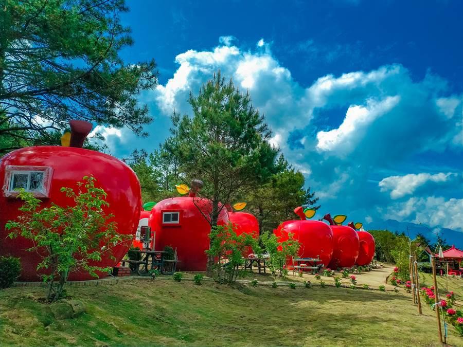 福壽山農場引進「蘋果屋」,鮮紅色的大蘋果與翠綠山林相映成趣。(王文吉翻攝)