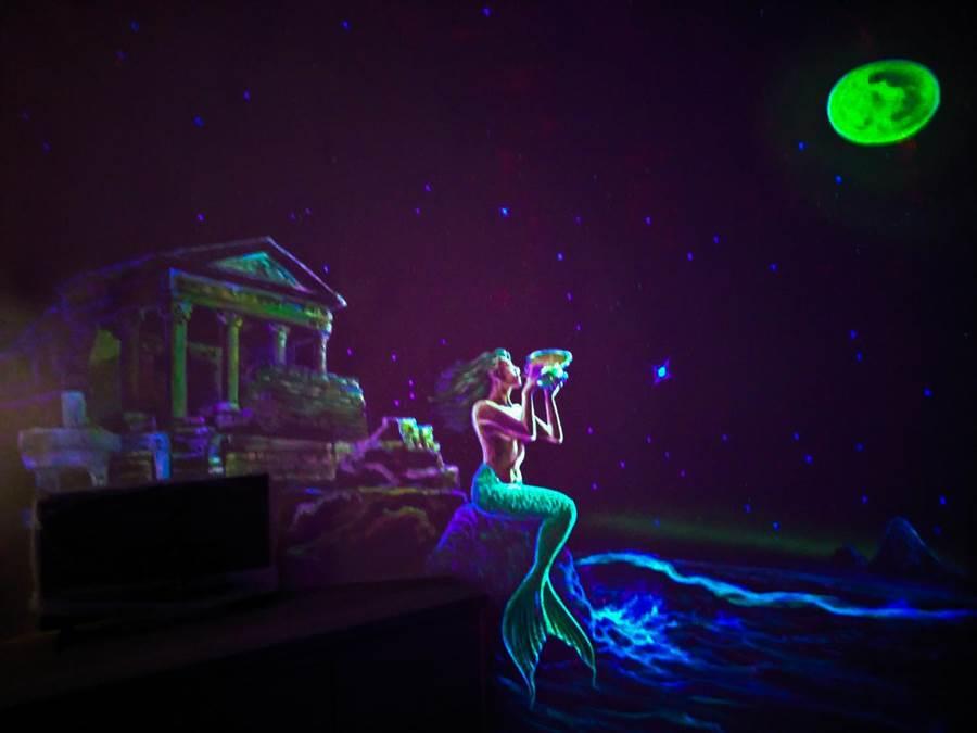 蘋果屋內設計手繪螢光畫,入夜關燈後人魚傳說躍然牆上。(王文吉翻攝)