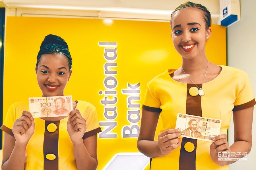 2015年7月22日,兩名工作人員在肯亞國家銀行新分行開業式展示肯亞先令(右)和人民幣鈔票。(新華社)