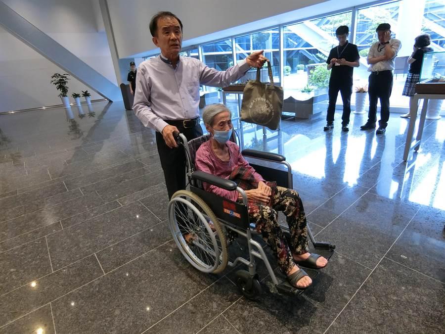 台中市議員段緯宇30日下午推著87歲黃姓阿嬤,手提阿嬤一個小小手提包是全部家當。(盧金足攝)