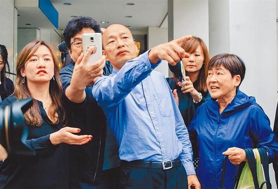 圖為高雄市長韓國瑜(中)去年11月28日在北市與媒體餐敘,眾多韓粉守候在餐廳外欲一睹風采,不顧韓正在接受採訪,爭先握手拍照,展現超高人氣。(資料照,郭吉銓攝)