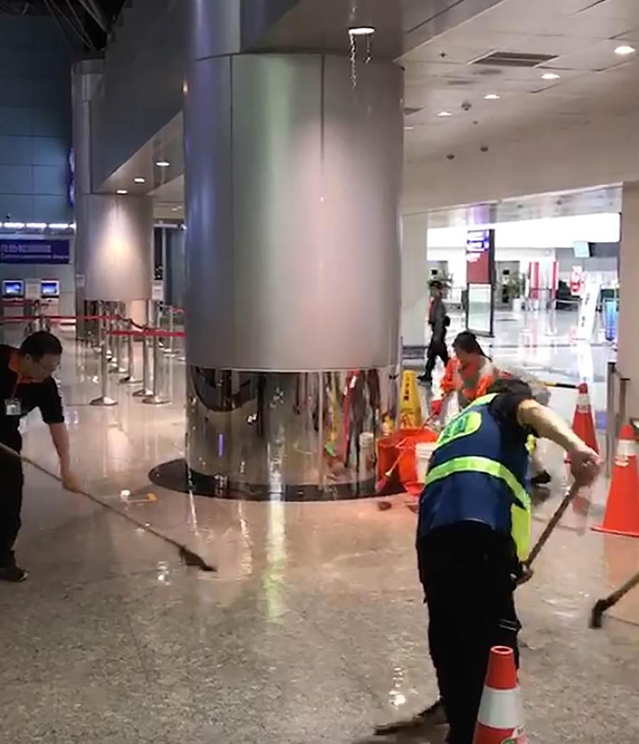 桃園機場在1日凌晨0時45分左右,傳出航廈內有滲水意外,在第2航廈出境6號櫃台與北側擴增報到櫃台中間的銜接處區域突然滲水情況,造成地板大片濕濘,清潔人員忙著清理。(翻攝畫面)