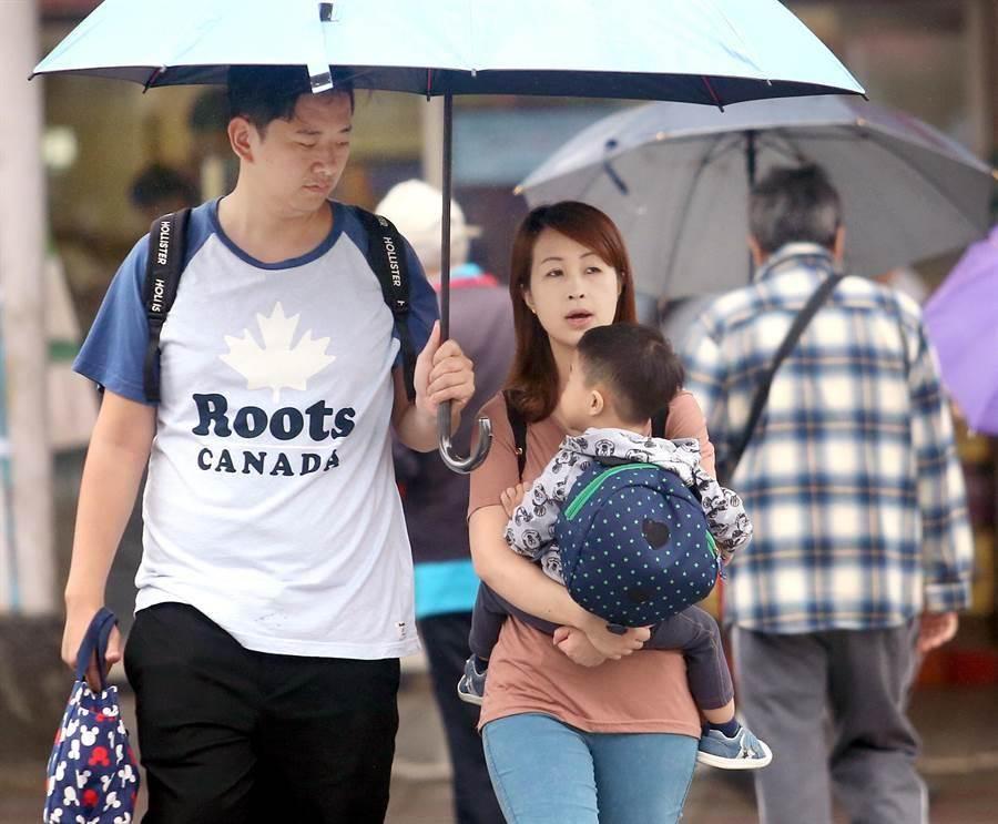 受鋒面通過及東北季風影響,台灣西半部及東北部地區1日普遍降雨,在台北市區行人紛紛撐傘避雨。(范揚光攝)