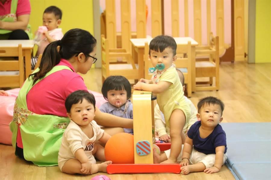 臺中市議會考察團30日北上參觀淡水新興公托中心,小朋友看著議員來訪,好奇的伸長脖子。(吳亮賢翻攝)