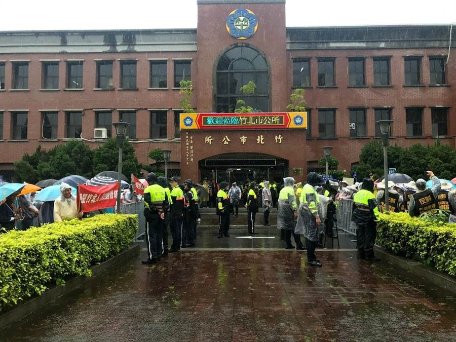 竹北市公所籌設第六公墓公園化納骨堂新建工程,反對者與支持者1日在市公所前聚集,警方出動人力到場維持秩序,雙方壁壘分明。(莊旻靜攝)
