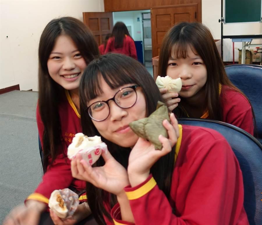 雲林縣虎尾大成商工學生把包子和粽子吃掉,象徵吃下「包中」,希望統測「包中」。(許素惠攝)