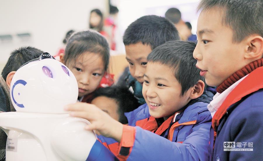 2018年12月21日,重慶舉辦科創體驗活動,小學生們了解機器人知識。(新華社)