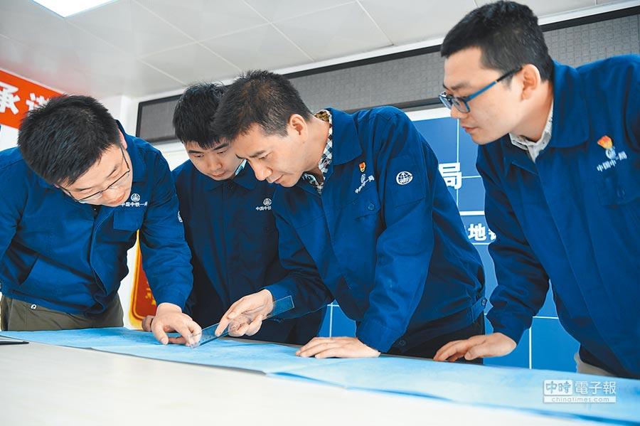 獲得「陜西青年五四獎章」的梁西軍(右二)在西安地鐵5號線與同事討論施工進展。(新華社)