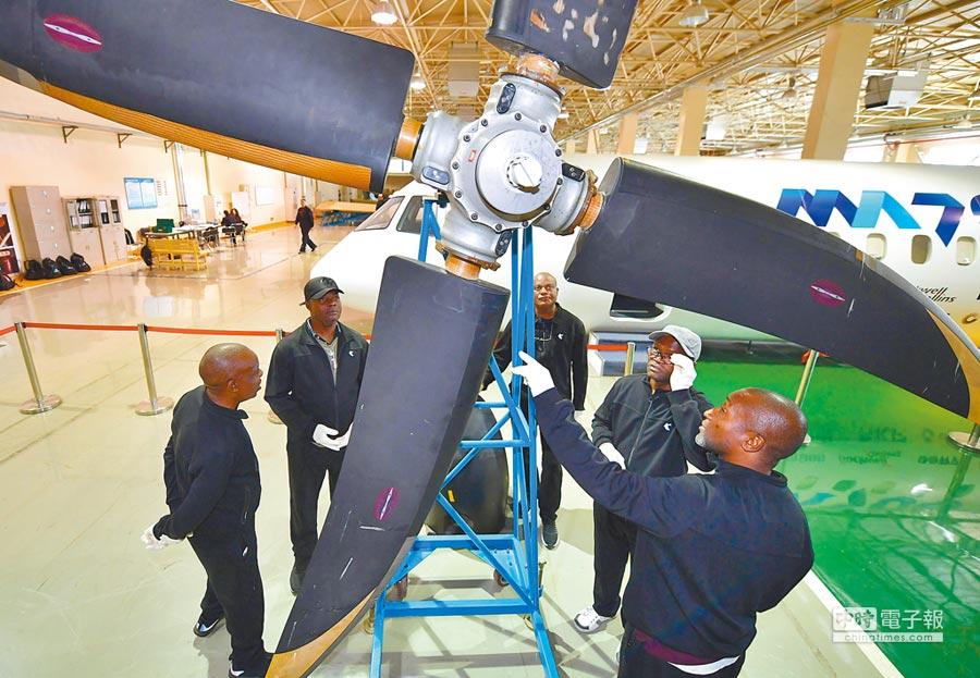 在西飛民機客戶服務中心維修實習車間內,安哥拉學員查看飛機螺旋槳的機械結構。(新華社)