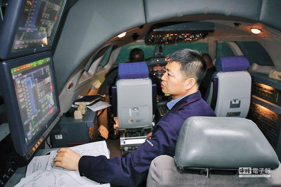西飛民機客戶服務中心教員鄭坤,在模擬機訓練艙內查看安哥拉學員的模擬飛行參數。(新華社)