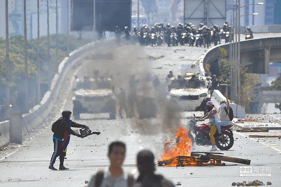瓜伊多的支持者與鎮暴警察在公路上對峙。(法新社)