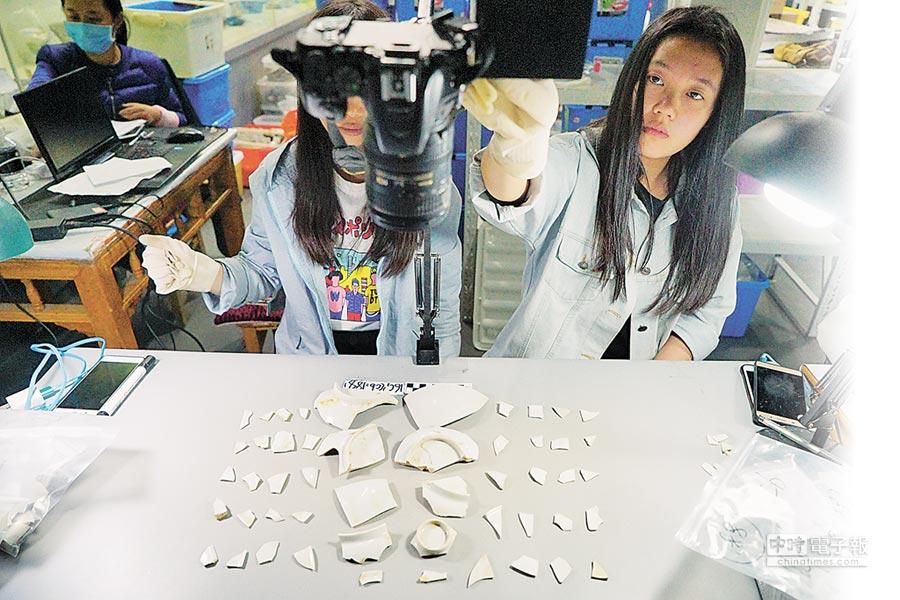 工作人員在對分揀的碎瓷片進行拍照留檔,方便後續修復。(新華社資料照片)