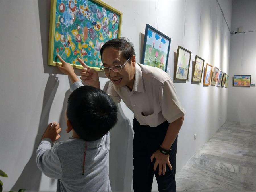 華大附小校長鮑明鈞(右)傾聽特教生說明自己的畫作內容。(范振和攝)