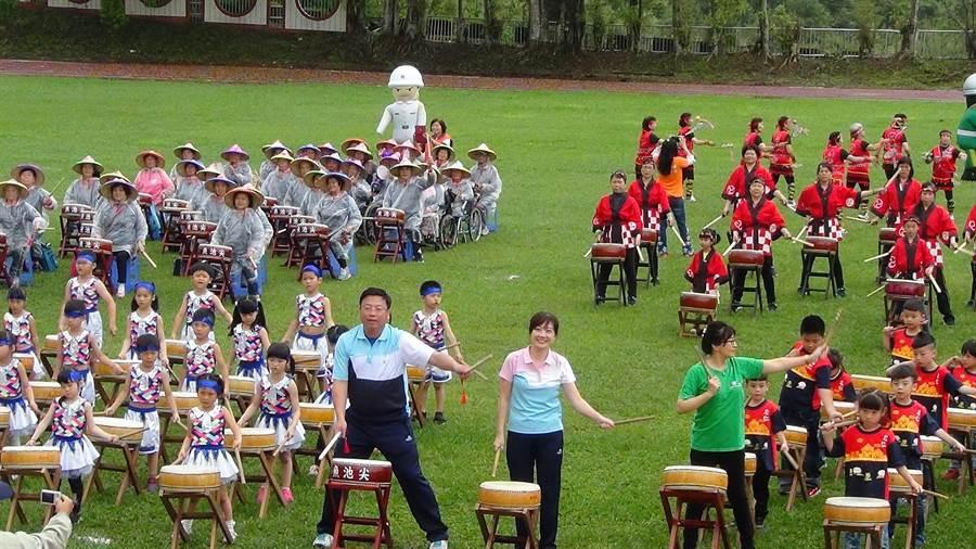 魚池鄉運開幕活動,鄉長劉啟帆(左一)與夫人施怡真(左二)與學童一起振臂擊鼓。(沈揮勝攝)