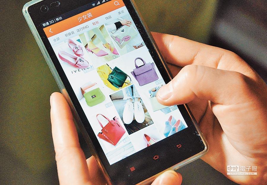 大陸年輕人愛買奢侈品。圖為福州市民使用手機上網購物。(中新社資料照片)