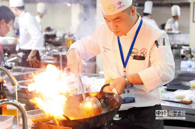 一名參加上海餐飲技能大賽的大廚在比賽中炒菜。(新華社資料照片)
