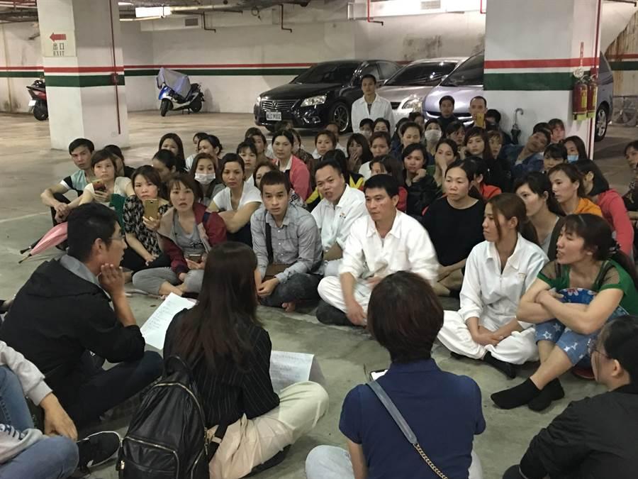 圖說:勞工局人員在地下室停車場席地而坐傾聽外籍勞工的訴求。(陳俊雄翻攝)