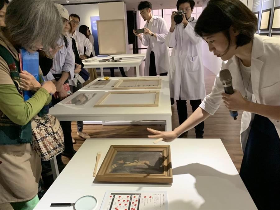 修復師李文元(右)現場導覽,實地進行「居家油畫保存的秘密」體驗活動。(王揚傑翻攝)