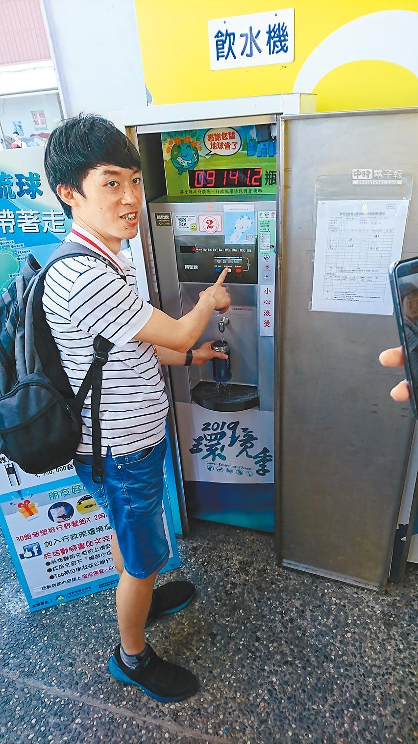 遊客使用環保杯到飲水機裝水,減少塑膠垃圾。(廖德修攝)