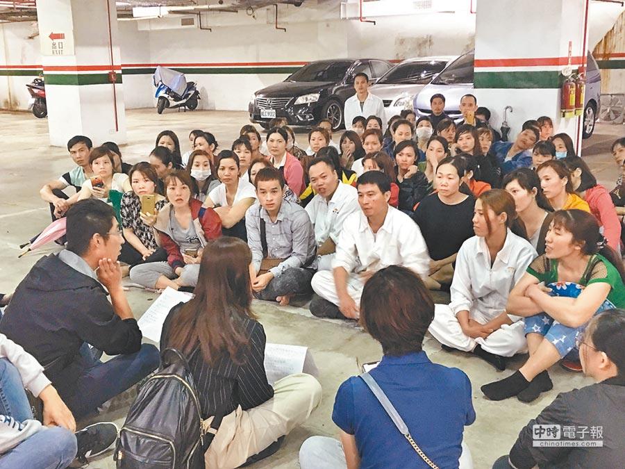 勞工局人員在地下室停車場席地而坐傾聽外籍移工的訴求。(陳俊雄翻攝)