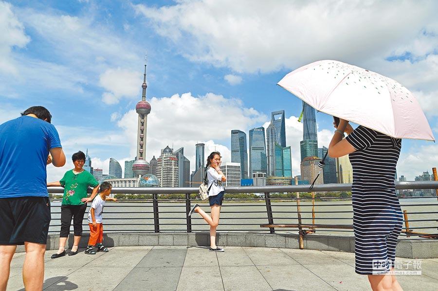 2018年7月10日,旅客在上海外灘遊玩,欣賞黃浦江兩岸美景。(中新社)