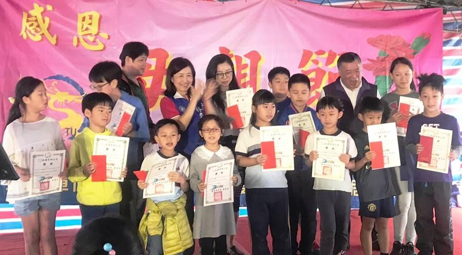 大安區龍圖里里長蕭萬居(右後二)頒發獎學金給社區的績優學生,這是送給媽媽最好的母親節禮物。(圖/永慶房屋提供)