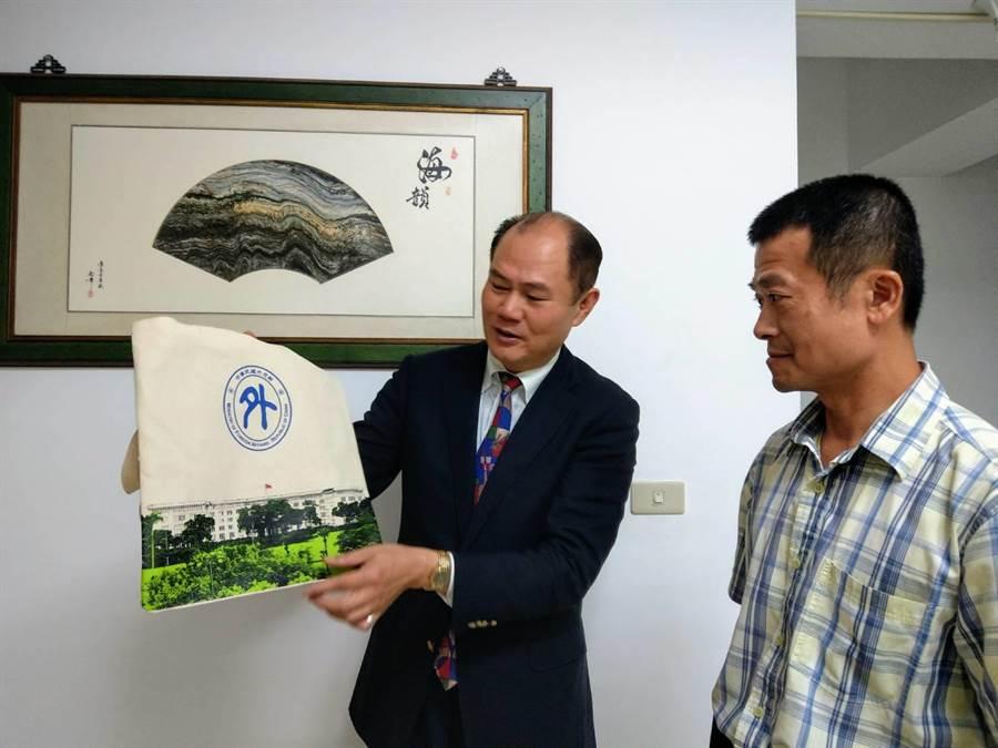 外交處東部辦事處長粘信士(左)舉例,請林信吉可用特色環保袋當伴手禮。(范振和攝)