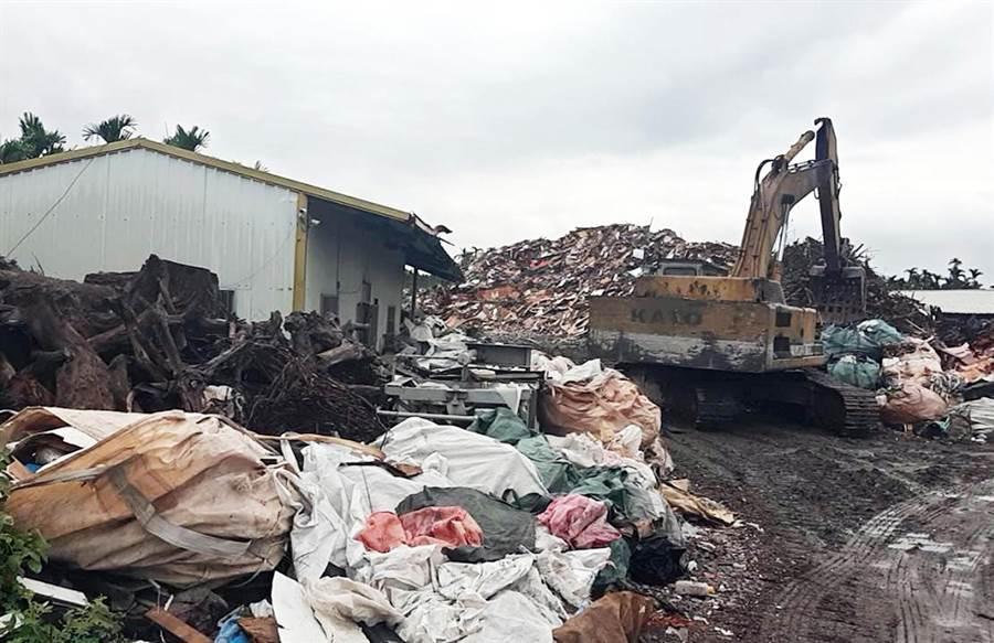 屏縣環保局於萬巒鄉農地查獲非法堆置廢棄物,現場宛如一座小型垃圾山,連稽查人員都直呼離譜。(林和生翻攝)