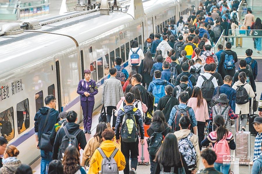 「五一」小長假迎來客流小高峰。圖為4月30日,旅客在南京火車站進站乘車。(新華社)