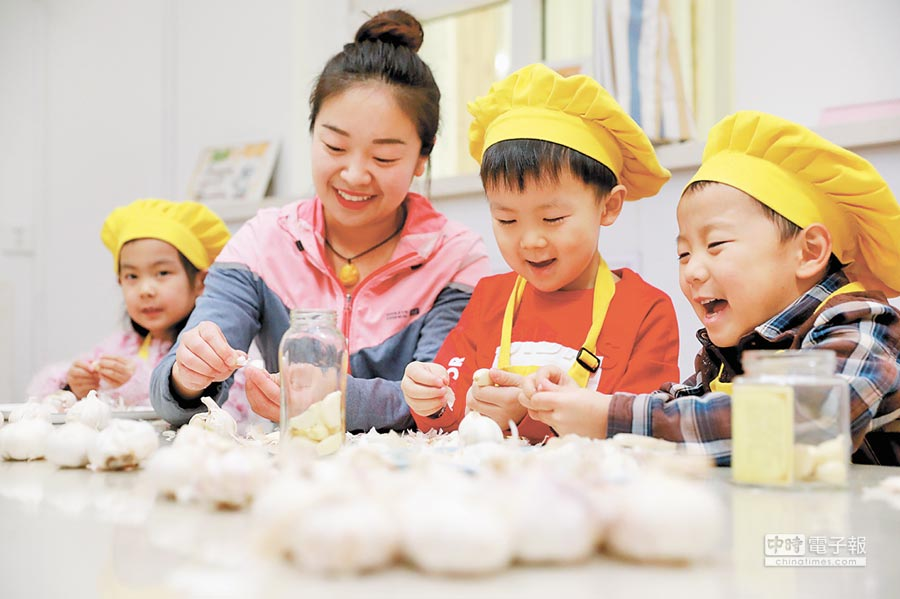 1月11日,在河北石家莊市第一幼兒園,老師和孩子們在剝蒜準備醃製臘八蒜。(新華社)