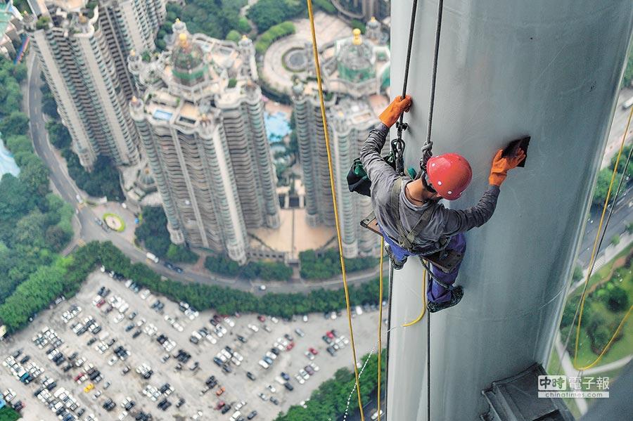 抖音視頻有點讚破億的清潔工。圖為2018年8月3日,高空清潔工使用濕布擦洗廣州塔108層外的鋼柱。(中新社)