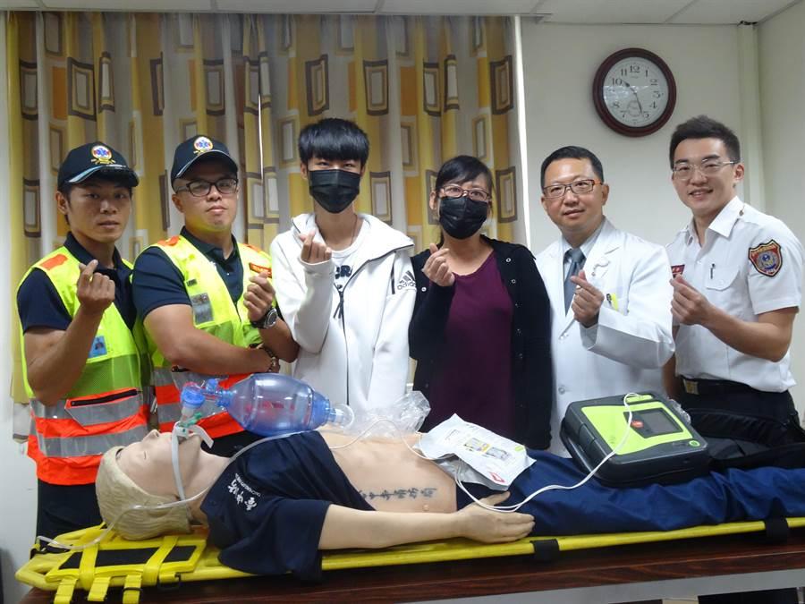 國三生(左三)跟媽媽(右三)在急診醫師和消防隊員陪同下一起現身,希望能讓更多民眾在緊急時刻也能像他們一樣透過119線上指導員協助,救回至親一命。(馮惠宜攝)
