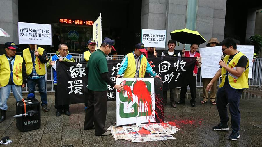 桃園產業工會與陳情者詹益協潑灑紅色液體,抗議血汗回收業者。(廖德修攝)