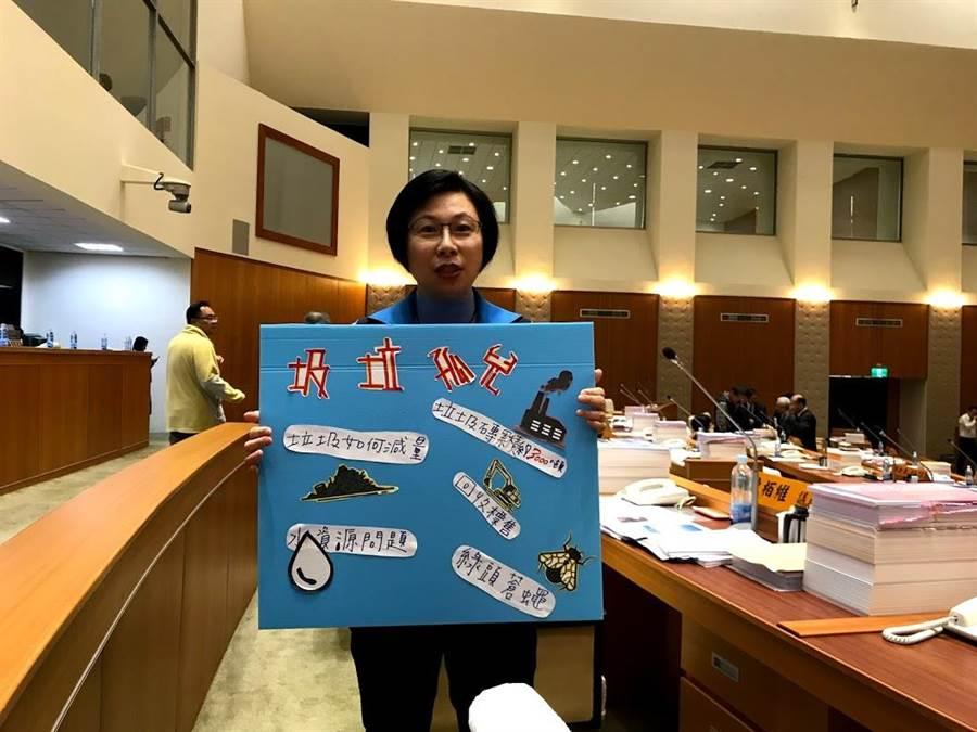 新竹縣議員吳淑君手持字卡,指出被資源回收商運回且無法利用的雜塑膠、雜質等垃圾,為「垃圾孤兒」,也孳生環境衛生問題。(莊旻靜攝)