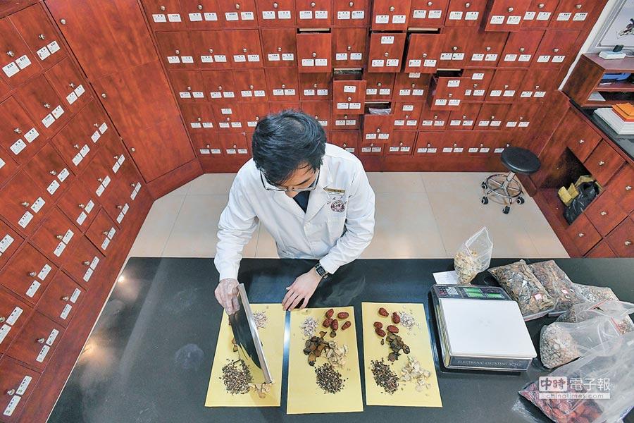 台灣青年就讀廣州中醫藥大學博士班,課餘之際,在工作的診所為顧客抓藥。(新華社資料照片)