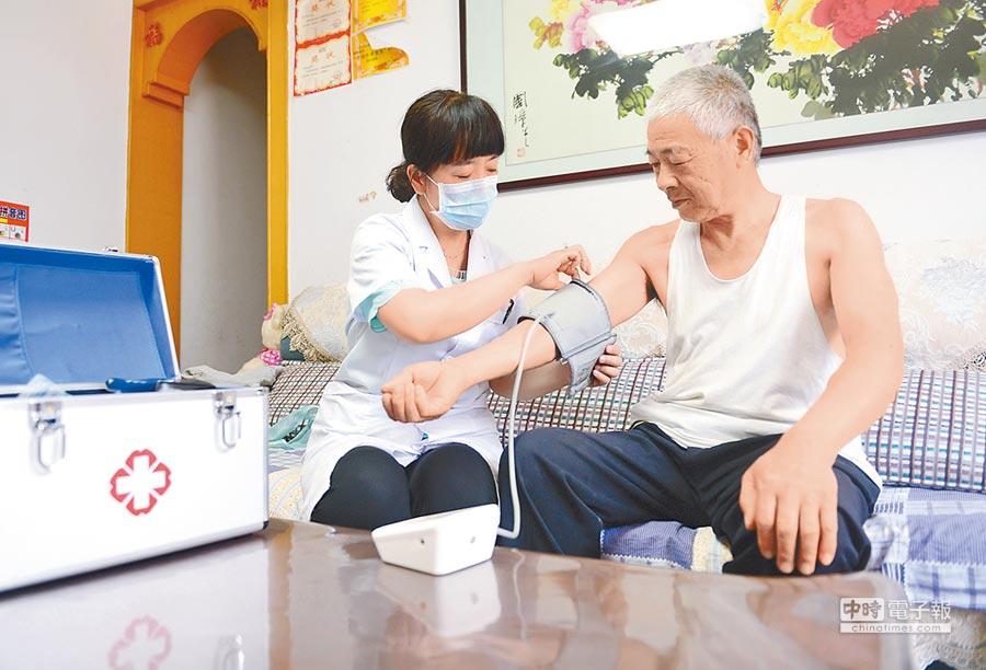 河北某社區,護士上門為老人測量血壓。(新華社資料照片)