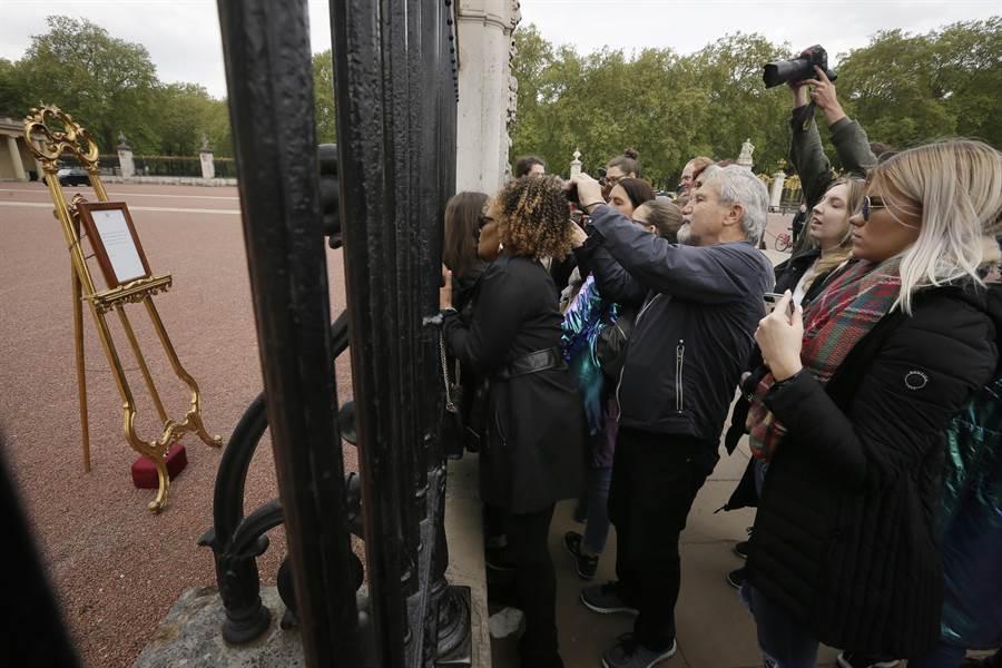 白金漢宮5月7日公告,梅根6日已生產,哈利王子喜獲麟兒,民眾紛紛在公告前照相留念。(美聯社)