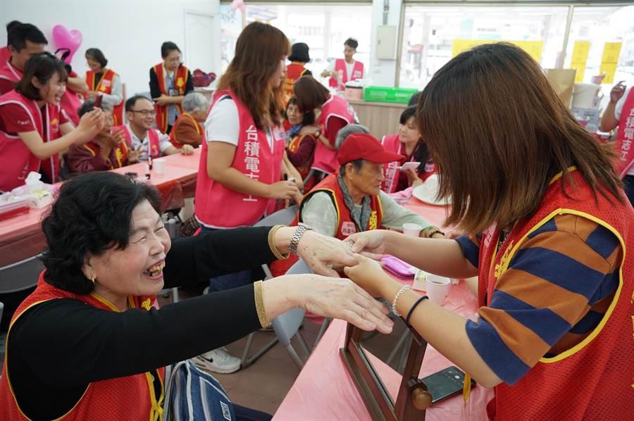 台積志工給阿嬤們化妝,一位阿嬤開心的向志工展現,擦過指甲油後的美麗雙手。(黃國峰攝)