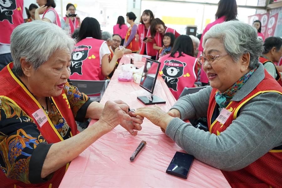 化妝活動中,二位阿嬤開心的互擦指甲油,玩得很愉快。(黃國峰攝)