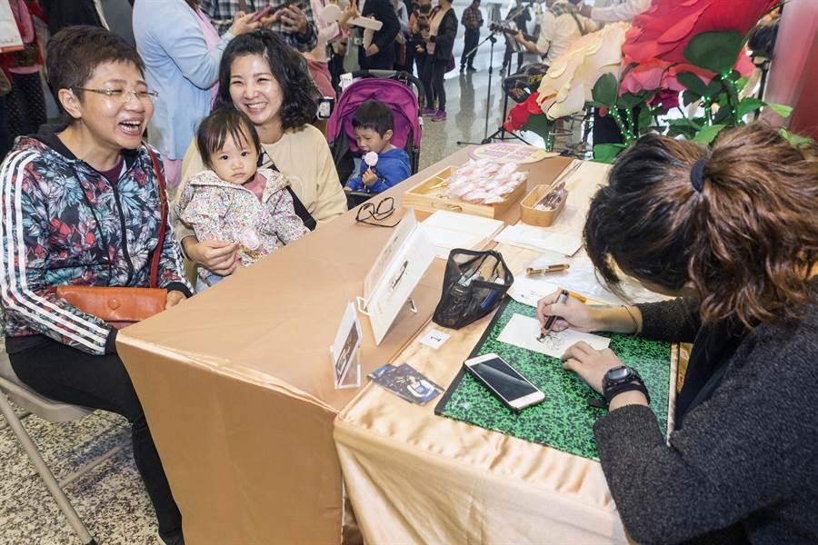 昇恆昌免稅店9日在桃園機場第1航廈提前舉行母親節慶祝活動,旅客只要參加點歌向母親示愛活動,並在活動背版前拍照上傳個人社群平台,就可獲得速寫師當場繪製,獨一無二的肖像插畫留做母親節紀念。(陳麒全攝)