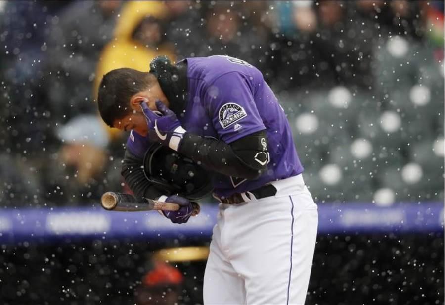 洛磯艾瑞納多脫下頭盔清理耳朵裡的雪。(美聯社)
