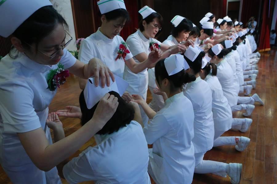 慈濟科技大學護理系今舉辦28屆加冠典禮,由護理系老師親自為學生加冠。(張祈翻攝)
