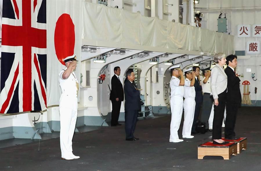 英國首相梅伊2017年訪日時,由日防衛大臣小野寺五典陪同登上出雲艦。(圖/美聯社)