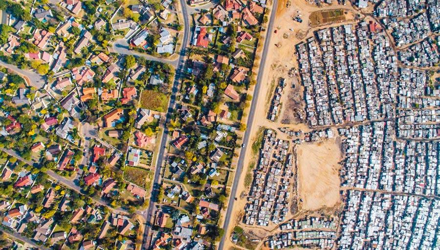 美國西雅圖攝影師米勒2016年用空拍機在約翰尼斯堡布魯伯斯蘭區上空捕捉到令人震撼的景象:一條馬路將兩個世界分隔,左邊是房價高昂的豪宅社區,右邊是遍布簡陋棚屋的貧民區。(圖取自unequalscenes.com)