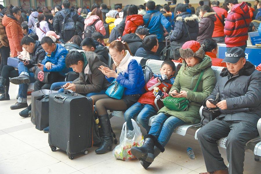 資通訊發達時代,人際關係反而隱藏在3C產品後面。圖為哈爾濱火車站候車室內,很多旅客在候車時低頭玩手機。(中新社資料照片)