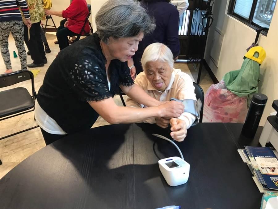 每天一早,周蓮香打開家門迎接上門的鄰里老朋友,並為大家測量、記錄血壓。(謝瓊雲攝)