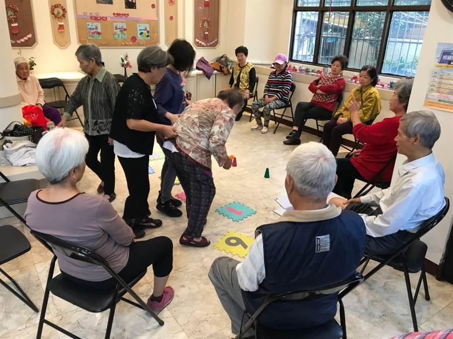 在社工與照服員偕同下,參加活動的長者們,聽從物理治療師的指示進行肌力訓練。(謝瓊雲攝)