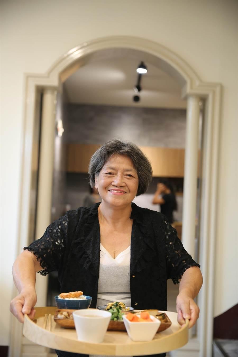 在廚房裡將秀老郎日照中心製作的午餐分裝盛盤後,74歲照服員周蓮香會一一為長者們端上餐桌。(謝瓊雲攝)
