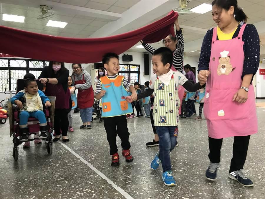 三峽日托慢飛天使在特教老師的帶領下,和三峽幼兒園孩子一起玩遊戲。(吳亮賢翻攝)