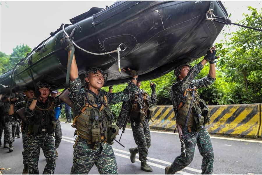 兩棲偵搜班成員合力抬起橡皮艇由岸際衝向海中。(圖/國防部提供)